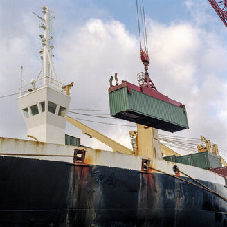 Shipping container being lowered by crane onto ship in port - CUF25752