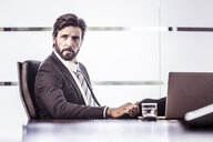 Confident businessman looking over shoulder from office desk - CUF25815