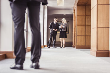 Senior businessman and woman talking in office corridor - CUF25833