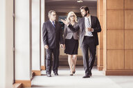 Businessmen and woman walking and talking in office corridor - CUF25839