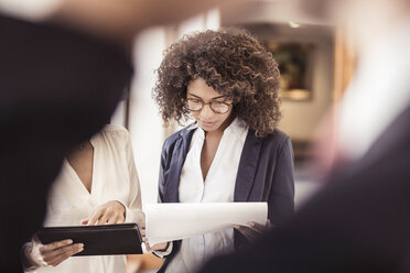 Young businesswoman reading paperwork in office - CUF25848