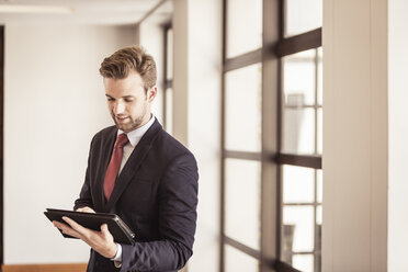 Young businessman using digital tablet touchscreen in office - CUF25854
