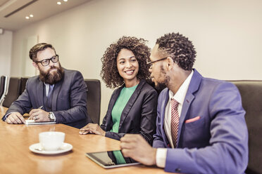 Young businesswoman talking at conference table meeting with businessmen - CUF25869