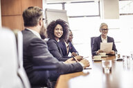 Businesswomen and men talking at conference table meeting - CUF25872