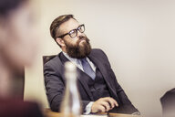 Businessman listening at boardroom meeting - CUF25875