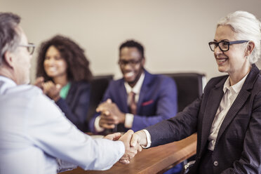 Mature businesswoman shaking hands with client at boardroom meeting - CUF25878