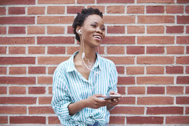 Portrait of relaxed woman using earphones and cell phone - ABIF00551