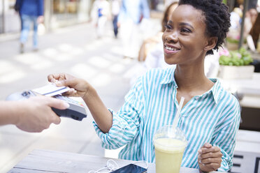 Portrait of smiling woman paying by credit card at pavement cafe - ABIF00563