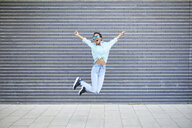 Happy woman jumping in the air in front of grey facade - ABIF00575