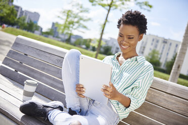 Portrait of smiling young woman with coffee to go sitting on bench looking at tablet - ABIF00578
