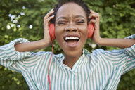 Portrait of singing young woman with headphones - ABIF00581