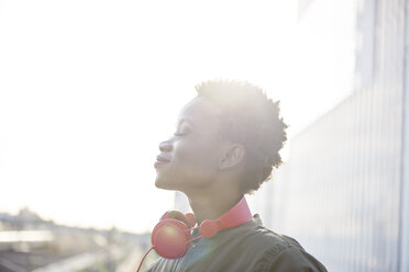 Profile of young woman with red headphones at backlight - ABIF00587