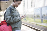 Young woman standing on platform looking at cell phone - ABIF00590