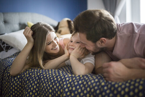 Happy family lying in bed, cuddling - AWF00015