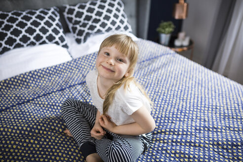 Blond little girl sitting on bed, smiling - AWF00036