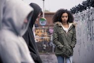 Teenagers standing against wall with graffiti - CUF25981