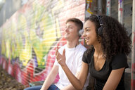 Teenage couple listening to mp3 player against wall with graffiti - CUF25984