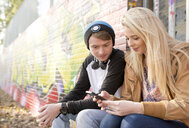 Teenage couple using smartphone against wall with graffiti - CUF25987