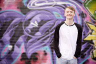 Teenager standing against wall with graffiti - CUF26011