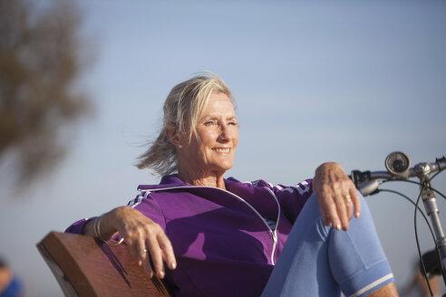 Senior woman enjoying ocean view on bench - CUF26029