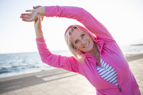 Senior woman stretching by beach - CUF26038