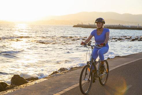 Senior woman cycling on beach - CUF26041