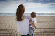 Rear view of mid adult woman and toddler daughter looking out to sea, Castelldefels, Catalonia, Spain - CUF26059