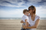 Mid adult woman kissing toddler daughter on beach, Castelldefels, Catalonia, Spain - CUF26062