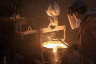 Worker raking molten steel in foundry - CUF26086