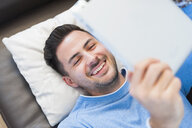 Young man reclining on sofa browsing digital tablet - CUF26110