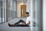 Young businessman sitting in office corridor using laptop - CUF26152
