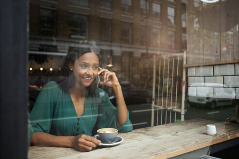 Mid adult woman chatting on smartphone in cafe window seat - CUF26371