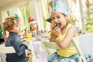 Portrait of girl eating cake at kids birthday party - CUF26425