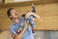 Man playing with toddler son in kitchen - CUF26431