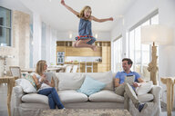 Girl jumping mid air from living room sofa whilst parents use digital tablet - CUF26437