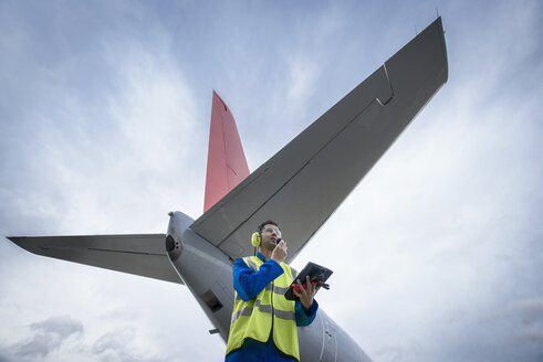Airside engineer talking on radio near aircraft on runway, low angle view - CUF26449