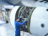 Engineer working on jet engine in aircraft maintenance factory - CUF26473