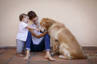 Mid adult woman with baby daughter petting dog in kitchen - CUF26482