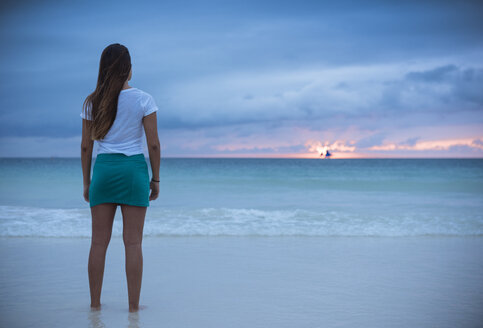 Rear view of young woman looking out to sea at sunset, Boracay Island, Visayas, Philippines - CUF26512