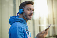 Mature man on city street choosing headphone music on smartphone - CUF26560