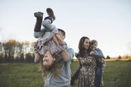 Young couple carrying son and daughter in field - CUF26602
