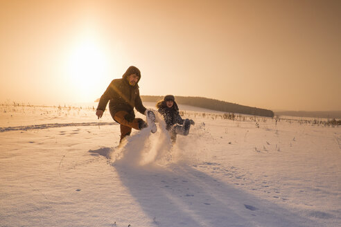 Man and son kicking snow powder at sunset, Sarsy village, Sverdlovsk Oblast, Russia - CUF26629