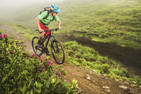 Young male mountain biker cycling next to stream - CUF26668