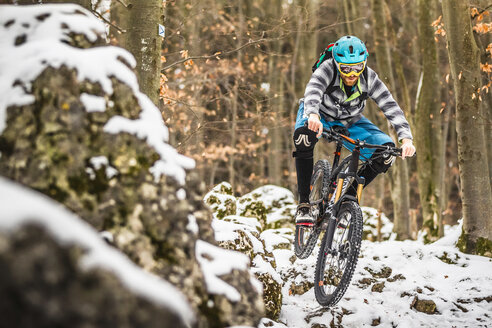 Young male mountain biker speeding on snow covered rocks in forest - CUF26677