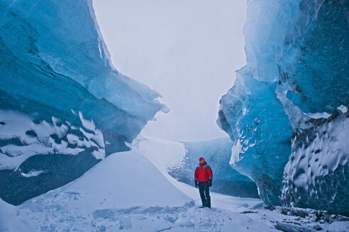 Mature man standing next to pile of snow exploring crystal ice cave, Breidamerkurjokull, Vatnajokull, Iceland - CUF26743