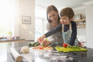 Mother and son preparing pizza together in kitchen - CUF26914