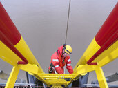 Offshore windfarm worker climbing turbine, high angle view - CUF26995