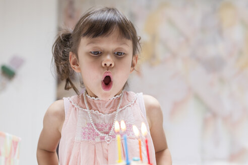 Portrait of little girl blowing out burning candles on her birthday cake - DRF01741