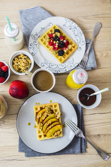 Various garnished waffles on breakfast table - GIOF03956