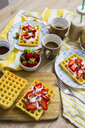 Waffles garnished with strawberries, Greek yogurt and almonds on breakfast table - GIOF03959